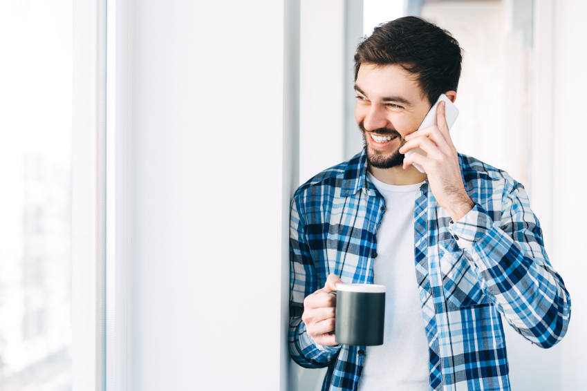 Man with cup of coffee smiling whilst talking on the phone