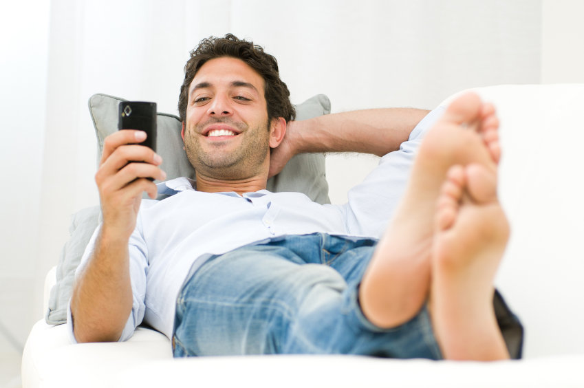 Man laying down smiling at his mobile phone